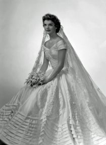 Jacqueline Bouvier The future first lady (and fashion icon) wore a voluminous ivory silk taffeta gown by the designer Ann Lowe when she married John F. Kennedy in 1953. A portrait neckline and wide, embellished skirt emphasized Jackie's small waist, and an heirloom lace veil, which originally belonged to her grandmother, completed the super-romantic ensemble.